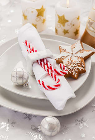 Place setting in white for Christmas with gingerbread cookie and candy cane photo