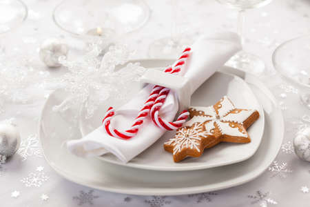 Place setting in white for Christmas with gingerbread cookie and candy cane