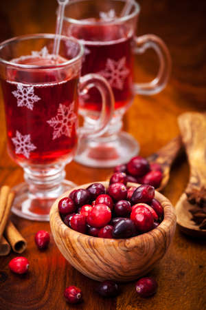 Cranberries in wooden bowl with hot mulled wine photo