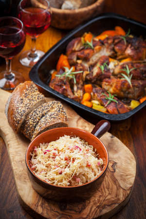Sauerkraut with roasted pork belly on vegetables and red wine photo
