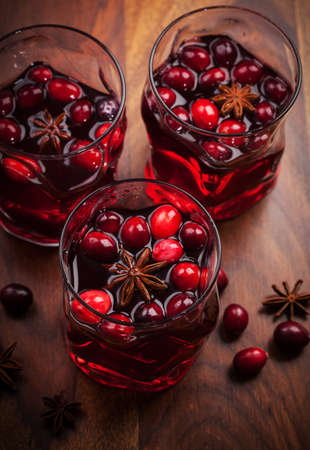 Hot drink with cranberries for Christmas on wooden table photo