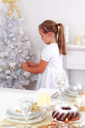 Cute girl decorating Christmas tree Stock Photo - 16796981