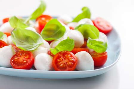 comida gourmet: Ensalada de tomate pequeño con mozzarella y albahaca