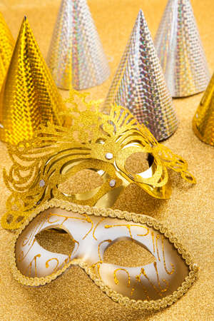 Party motive with carnival mask and party hat in golden tone photo
