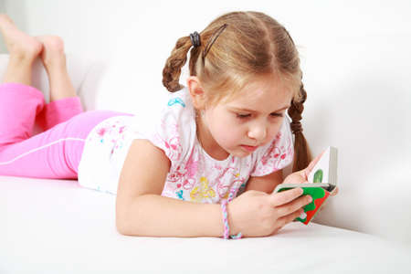 Small girl relaxing and reading photo