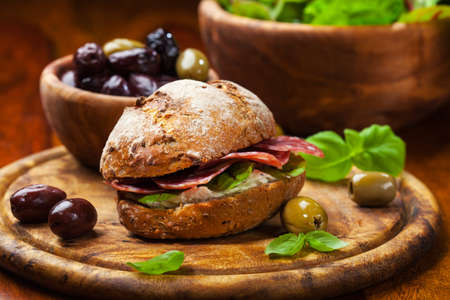 Sandwich with Italian salami, goat cheese and fresh olives photo