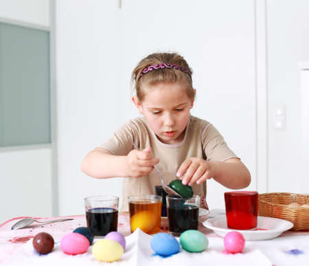 Portrait of schoolgirl painting Easter eggs photo
