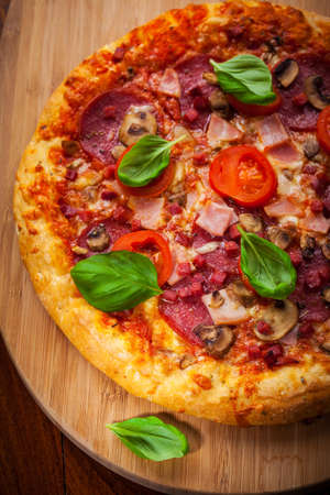 Homemade traditional pizza with salami and mushrooms photo