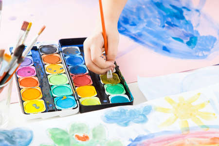 Detail of child's hand painting with watercolor