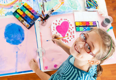 playtime: Schoolgirl painting with water color - top view