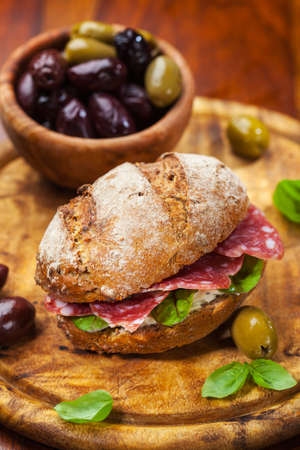 Whole grain sandwich with Italian salami, goat cheese and fresh olives photo