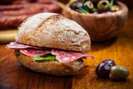 salame: Grano intero panino con salame italiano, formaggio di capra e olive fresche Archivio Fotografico