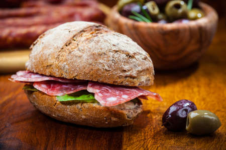 Whole grain sandwich with Italian salami, goat cheese and fresh olives
