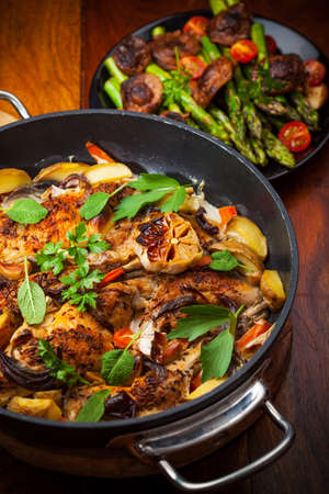 Roasted roasted rabbit on vegetables in pan Stock Photo