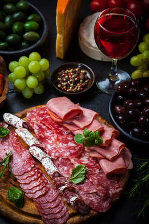 Meat catering platter with olives and red wine