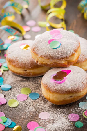 Krapfen, Berliner or  donuts with streamers and confetti. Colorful carnival or birthday image Stok Fotoğraf