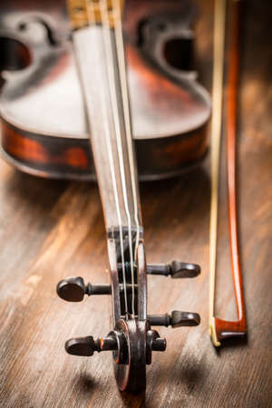 Detail of old violin and bow in vintage style on wood background