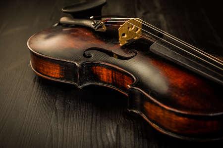 Nahaufnahme der alten Violine und Streicher im Vintage-Stil auf Holzhintergrund