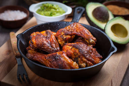Grilled hot and spicy chicken wings with spices on dark background Stockfoto - 130050359