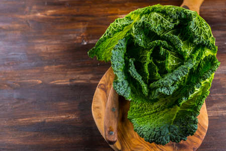 Fresh raw savoy cabbage with garlic and knife on wooden background Stock Photo