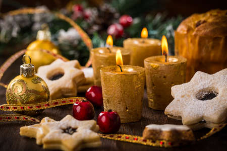 Christmas still life with homemade cookies and candles on wooden background