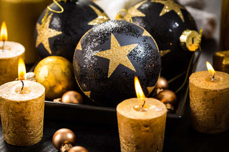 Christmas still life with ornaments and candles on wooden background Stock Photo