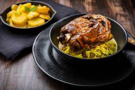 Roaster Pork Knuckle with savoy cabbage and baked potatoes - Traditional German cuisine, Eisbein, Schweinehaxe Stock Photo