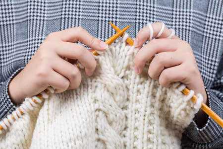 Close up of hands knitting warm sweater Stock Photo