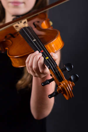 Close up of professional violin in hands of little girl playing it on black background Stock Photo