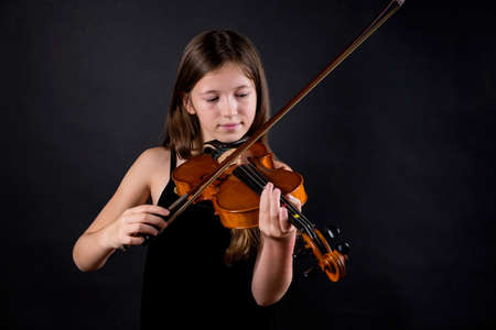 Young professional violinist playing and exercising on black background