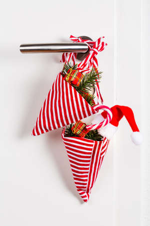 Small Christmas bag with branch and candy cane hanging on door handle on white