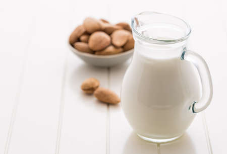 Jar of almond milk with almond nuts on white