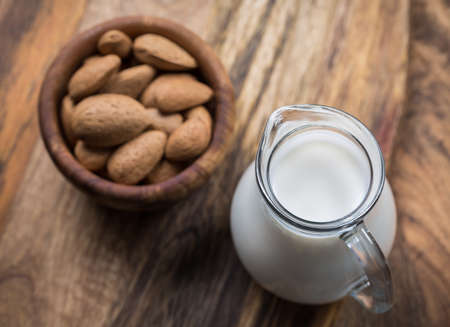 Jar of almond milk with almond nuts on wooden