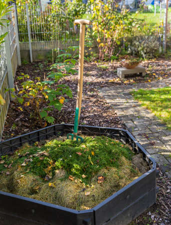 Making compost in composting bin in small garden Stock Photo