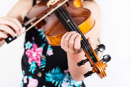 Close up of professional violin in hands of little girl playing it on white background