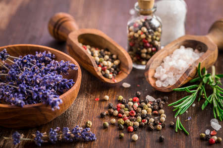 Still life with salt, pepper, fresh  rosamary and lavender on wooden background Stok Fotoğraf