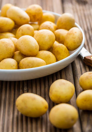 Fresh organic small potatoes in bowl with knife on wooden background