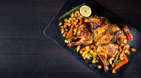 Butterflied grilled whole chicken with roasted vegetables and potatoes. Roadkill chicken style with herbs and lemon.