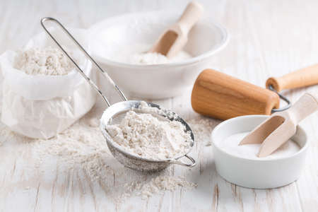 Spelt flour, sugar with baking ingredients and kitchen utensils on white wooden table.