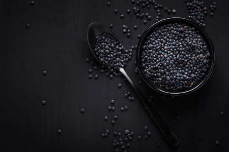 Beluga lentils on black background. Black lentils in bowl with spoon. Zdjęcie Seryjne