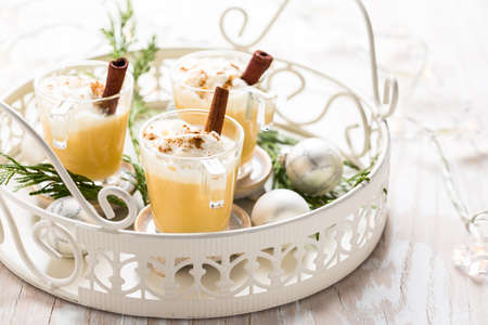 Eggnog with cinnamon and nutmeg for Christmas and winter holidays. With Xmas decorations on wooden background.