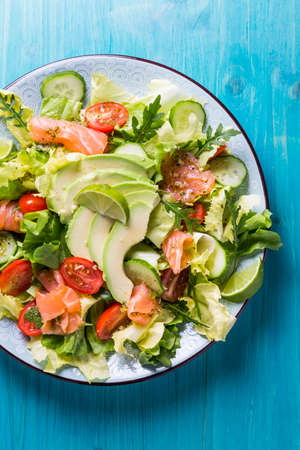 Healthy salad with smoked samlmon and avocado on cyan vackground Banque d'images