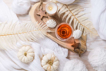Cosy still life for winter and autumn with glas of pink wine, pumpkin cookie, woll and warm sweater Foto de archivo