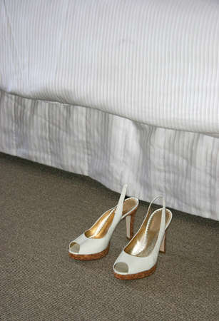 A pair of womens shoes next to a hotel bed.