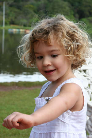 A little girl with an insect on her arm.