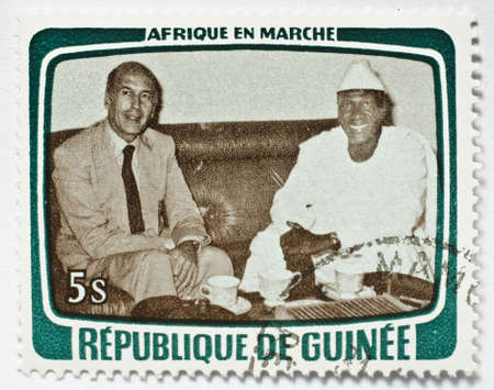 Stamp from Guinea shows image of a foreign dignitary and local host sitting down, from the Africa in Motion series, circa 1979