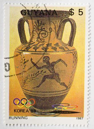 vasi greci: GUYANA - CIRCA 1987 un francobollo da Guyana mostra l'immagine di un antico vaso greco raffigurante un uomo che correva e commemora la Seoul 88 Olimpiadi, circa 1987 Editoriali