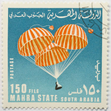 MAHRA SULTANATE - CIRCA 1967  A stamp from Mahra Sultanate  present day Yemen  shows image of a capsule parachuting back to Earth from space, possibly commemorating Project Gemini, circa 1967
