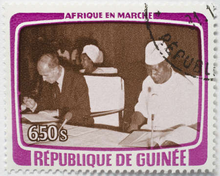 GUINEA - CIRCA 1979  A stamp from Guinea shows image of a foreign dignitary and local host sitting down signing some documents, from the Africa in Motion series, circa 1979
