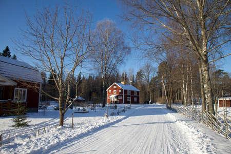 woden: Red wooden house in snowlandscape under bright blue sky in sweden